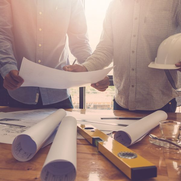 Architect and businessman reviewing building plans